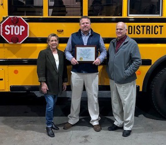 transportation staff in front of bus with certificate