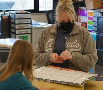 student working with teacher at table wearing masks